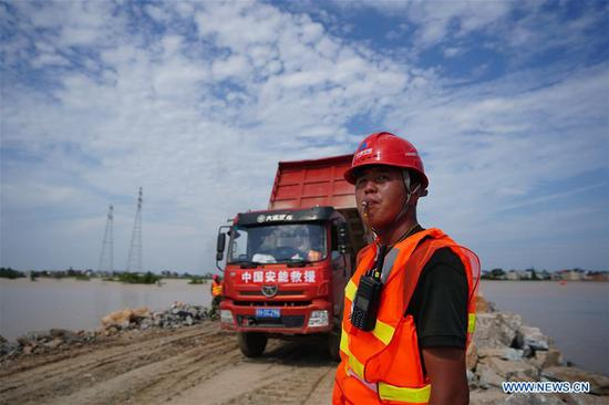 Staff members work at the construction site of a breached dyke in Poyang Town of Poyang County, east China's Jiangxi Province, July 12, 2020. The embankment of a river in east China's Jiangxi Province was breached late Wednesday following continuous torrential rains, forcing over 9,000 residents to evacuate. (Xinhua/Zhou Mi)