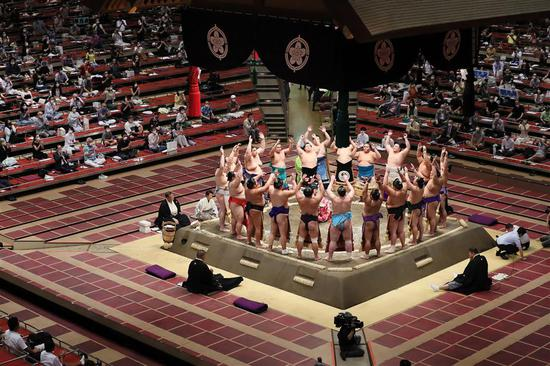 People observe social distancing as wrestlers perform a ceremony ahead of a new two-week sumo tournament at the Ryogoku Kokugikan, the main sumo arena in Tokyo, on Sunday.