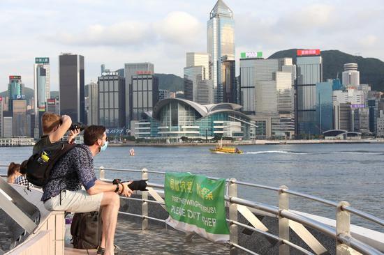 Visitors take photos of Hong Kong Island in south China's Hong Kong, July 14, 2020. (Xinhua/Wu Xiaochu)