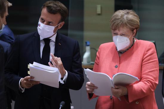 French President Emmanuel Macron (L) and German Chancellor Angela Merkel prepare to attend a special EU summit in Brussels, Belgium, July 20, 2020. (European Union/Handout via Xinhua)