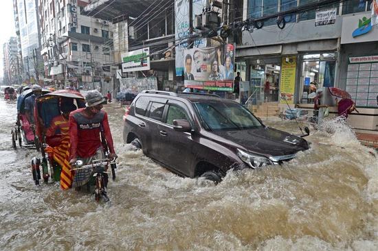Commuters make their way through a water-logged street after a heavy downpour in Dhaka on Tuesday. The death toll from heavy monsoon rains across South Asia has climbed to nearly 200.