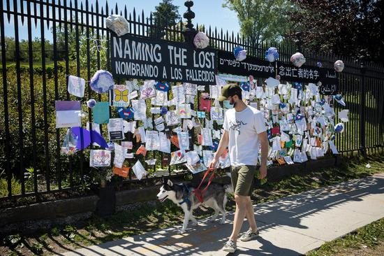 A man wearing a face mask walks past a memorial for COVID-19 victims in front of Green-Wood Cemetery in Brooklyn of New York, the United States, May 27, 2020. (Photo by Michael Nagle/Xinhua)