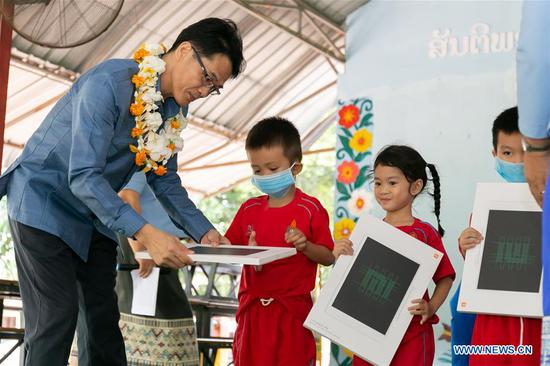 A child receives a smart board from a representative of the Chinese embassy in Laos during a handover ceremony in Vientiane, Laos, July 23, 2020. The Chinese embassy in Laos has donated 500 electronic smart boards to Lao kids in the affiliated kindergarten of the National University of Laos (NUOL) in capital Vientiane. (Photo by Kaikeo Saiyasane/Xinhua)