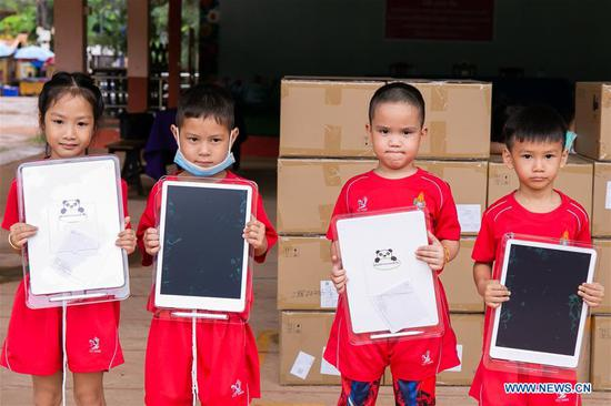 Kindergarten children pose for a group photo with smart boards in Vientiane, Laos, July 23, 2020. The Chinese embassy in Laos has donated 500 electronic smart boards to Lao kids in the affiliated kindergarten of the National University of Laos (NUOL) in capital Vientiane. (Photo by Kaikeo Saiyasane/Xinhua)