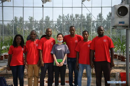 Zigani Saturnin (1st R) and his schoolmates pose for a photo at an agricultural experimental base in Quzhou County, north China's Hebei Province, July 23, 2020. Zigani Saturnin, a student from Burkina Faso, took part in agricultural practice activities at an agricultural experimental base with other 26 foreign students from China Agricultural University during this summer vacation, he hoped that he could apply the agricultural knowledge learned in China to practice while back to his country in the future. (Xinhua/Zhu Xudong)