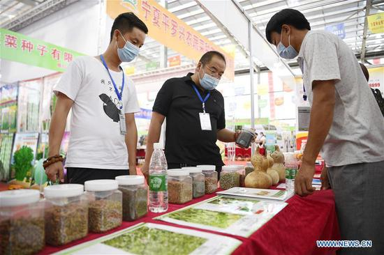 Participants learn about seed products during the 7th Ningxia Seeds Expo held at Pingluo County of Shizuishan City, northwest China's Ningxia Hui Autonomous Region, July 27, 2020. (Xinhua/Wang Peng)