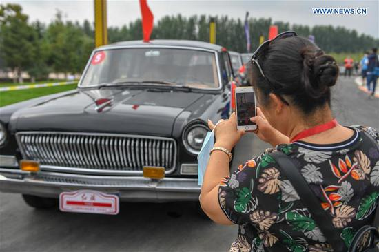 A visitor takes pictures of a limousine during an event showcasing the products and culture of China's iconic auto brand Hongqi in Changchun, northeast China's Jilin Province, July 28, 2020. (Xinhua/Zhang Nan)