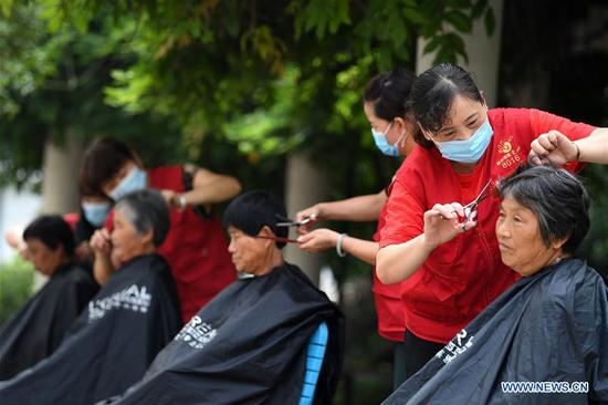 Volunteers cut hair for villagers at a temporary shelter in a school at Feixi County, east China's Anhui Province, July 29, 2020. Affected by floods, over 200 villagers in Fengle Town of Hefei were transferred to the school. Volunteers at the temporary shelter helped with the conveying of flood relief materials, food distribution, health care services, homework tutorship and free hairdressing services. (Xinhua/Liu Junxi)