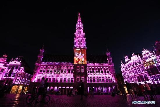 People watch a sound and light show at the Grand Place in Brussels, Belgium, July 29, 2020. A sound and light show was held at the Grand Place of Brussels to highlight Belgium's missing events in this summer due to the COVID-19 pandemic. (Xinhua/Zheng Huansong)