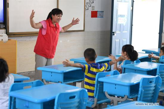 A volunteer teaches singing to children at a temporary shelter in a school at Feixi County, east China's Anhui Province, July 29, 2020. Affected by floods, over 200 villagers in Fengle Town of Hefei were transferred to the school. Volunteers at the temporary shelter helped with the conveying of flood relief materials, food distribution, health care services, homework tutorship and free hairdressing services. (Xinhua/Liu Junxi)