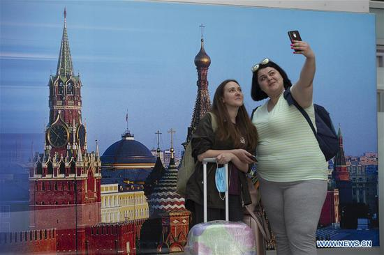 Passengers take a selfie at the Sheremetyevo International Airport in Moscow, Russia, on Aug. 1, 2020. Russia has partially resumed its international flights starting Aug. 1, according to reports. (Photo by Alexander Zemlianichenko Jr/Xinhua)