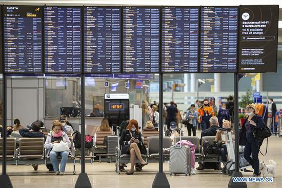 Passengers sit under a flight information board at the Sheremetyevo International Airport in Moscow, Russia, on Aug. 1, 2020. Russia has partially resumed its international flights starting Aug. 1, according to reports. (Photo by Alexander Zemlianichenko Jr/Xinhua)