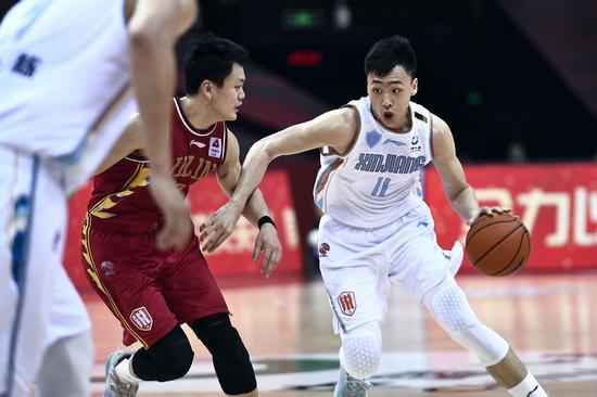 Qi Lin (R) of Xinjiang Flying Tigers controls the ball during a match against the Jilin Northeast Tigers in the 2019-20 Chinese Basketball Association (CBA) league in Qingdao, July 7, 2020. (Xinhua/Guo Xulei)