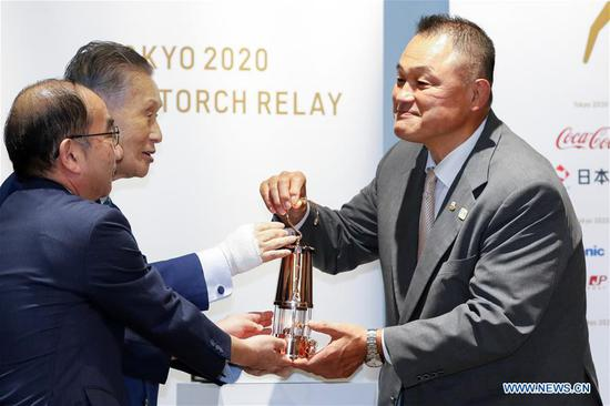 Japanese Olympic Committee President Yasuhiro Yamashita (R) receives the Olympic Flame from the Tokyo 2020 President Yoshiro Mori during the display ceremony at the Japan Olympic Museum in Tokyo, Japan on Aug. 31, 2020. The Tokyo Olympic flame, which had been kept in a secret place since the Games was postponed, has been put on display at the Japan Olympic Museum on Monday. A simple ceremony was held by Tokyo 2020 organizers and the Japanese Olympic Committee (JOC) to mark the opening of the public display, which will run from September 1 to November 1. (Xinhua/Pool/Rodrigo Reyes Marin)