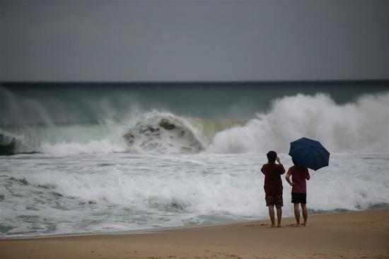 Two men watch the high waves brought by Typhoon Maysak on Haeundae beach in Busan on Wednesday.