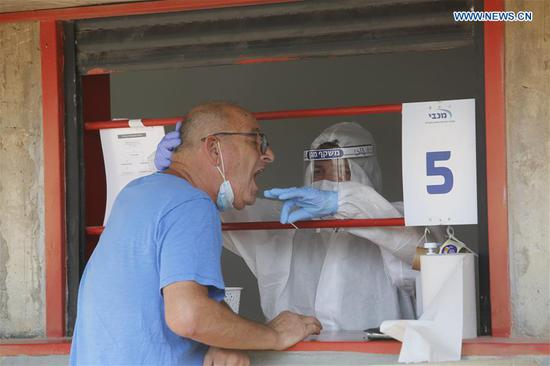 A medical worker takes a sample from a man for COVID-19 test in the central Israel city of Rishon Letsiyon on Sept. 6, 2020. The death toll in Israel over the COVID-19 surpassed 1,000 on the weekend, and the country also has one of the highest daily infection rates per capita in the world. (Photo by Gil Cohen Magen/Xinhua)