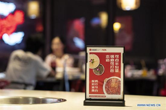 A sign promoting food waste reduction is placed on a table at a hot-pot restaurant in Chengdu, southwest China's Sichuan Province, Sept. 7, 2020. Many hot-pot restaurants in Chengdu have introduced measures such as offering smaller portions of food and takeaway services in their campaigns against food waste. (Xinhua/Li Mengxin)