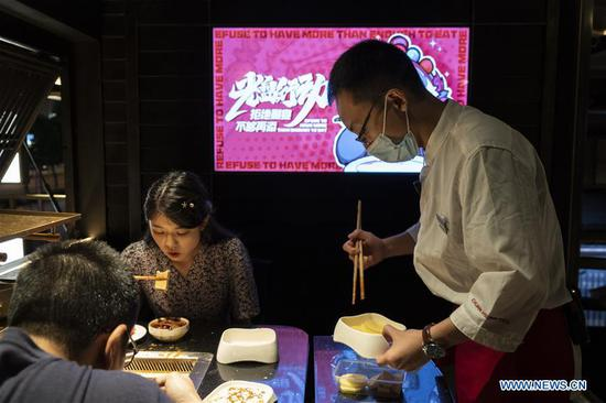 A staff member packs up leftover hot-pot ingredients for customers at a hot-pot restaurant in Chengdu, southwest China's Sichuan Province, Sept. 7, 2020. Many hot-pot restaurants in Chengdu have introduced measures such as offering smaller portions of food and takeaway services in their campaigns against food waste. (Xinhua/Li Mengxin)