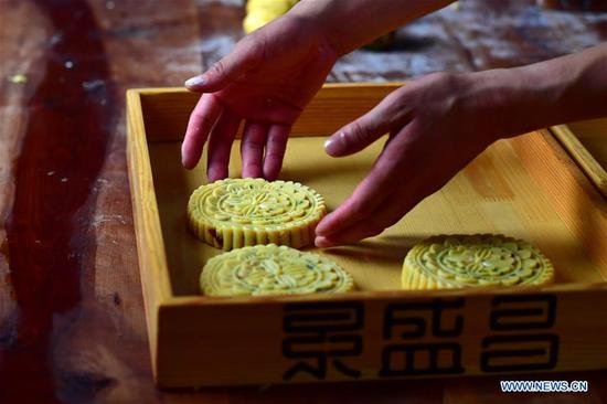 Zhang Xu puts away mooncakes ready for baking at the mooncake bakery Jingshengchang in Xiayi County, Shangqiu, central China's Henan Province, Sept. 13, 2020. At age 31, Zhang Xu already serves as the chef of Jingshengchang, a Henan-based mooncake bakery established in 1860. Mooncakes produced at Jingshengchang are characterized by their crispy crusts and generous stuffing, coupled with a meticulous set of bakery skills which Zhang had begun to learn since high school graduation in 2007.