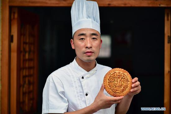 Zhang Xu shows a freshly-baked mooncake at the mooncake bakery Jingshengchang in Xiayi County, Shangqiu, central China's Henan Province, Sept. 13, 2020. At age 31, Zhang Xu already serves as the chef of Jingshengchang, a Henan-based mooncake bakery established in 1860. Mooncakes produced at Jingshengchang are characterized by their crispy crusts and generous stuffing, coupled with a meticulous set of bakery skills which Zhang had begun to learn since high school graduation in 2007.