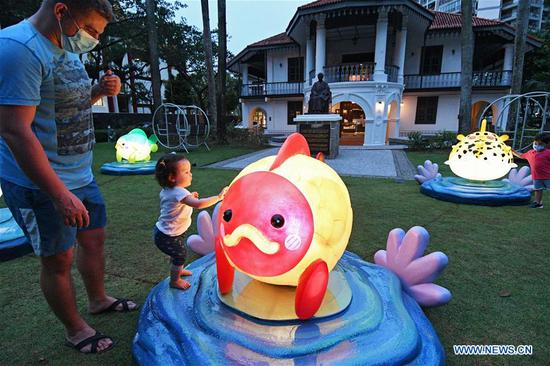 A child touches a lantern installation during celebrations for the upcoming Mid-Autumn Festival in Singapore, Sept. 14, 2020. (Photo by Then Chih Wey/Xinhua)