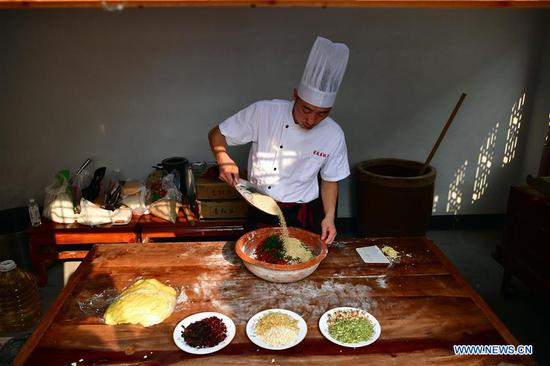 Zhang Xu prepares mooncake stuffing at the mooncake bakery Jingshengchang in Xiayi County, Shangqiu, central China's Henan Province, Sept. 13, 2020. At age 31, Zhang Xu already serves as the chef of Jingshengchang, a Henan-based mooncake bakery established in 1860. Mooncakes produced at Jingshengchang are characterized by their crispy crusts and generous stuffing, coupled with a meticulous set of bakery skills which Zhang had begun to learn since high school graduation in 2007.