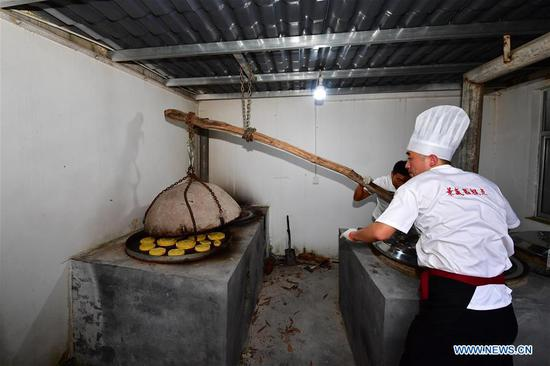 Zhang Xu (R) bakes mooncakes at the mooncake bakery Jingshengchang in Xiayi County, Shangqiu, central China's Henan Province, Sept. 13, 2020. At age 31, Zhang Xu already serves as the chef of Jingshengchang, a Henan-based mooncake bakery established in 1860. Mooncakes produced at Jingshengchang are characterized by their crispy crusts and generous stuffing, coupled with a meticulous set of bakery skills which Zhang had begun to learn since high school graduation in 2007.