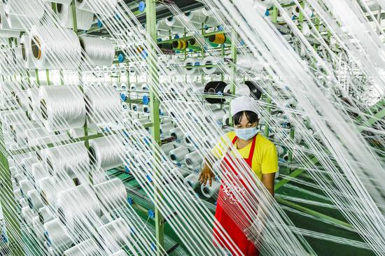 A worker is seen at a fiber factory in Zunhua City, north China's Hebei Province, July 16, 2020. China's economy bounced back to growth in the second quarter this year as the country gradually resumed work and production after having the COVID-19 epidemic effectively contained, official data showed. (Photo by Liu Mancang/Xinhua)