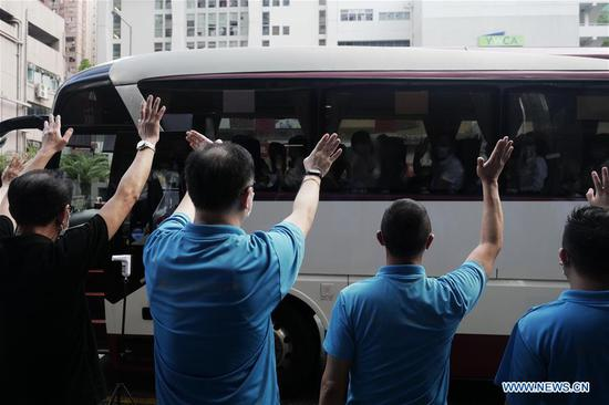 Staff members of a hotel wave goodbye to members of mainland nucleic acid test support teams in Hong Kong, south China, Sept. 16, 2020. (Xinhua/Wang Shen)