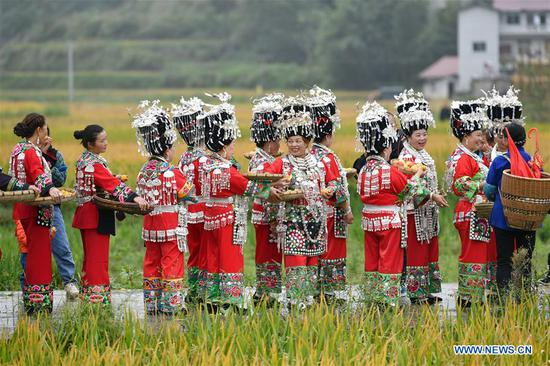 People in traditional costumes tour for bumper harvest at Dangzao Village of Panshi Town in Tongren City, southwest China's Guizhou Province, Sept. 20, 2020. Various activities are being held across the country to welcome the third Chinese farmers' harvest festival which falls on Sept. 22. (Photo by Long Enze/Xinhua)