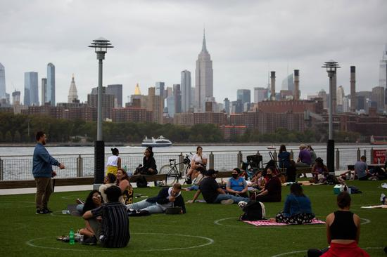 People sit in social distancing markers at Domino Park in New York, the United States, Sept. 13, 2020. (Photo by Michael Nagle/Xinhua)