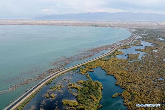 Aerial photo taken on Oct. 12, 2019 shows a riverbank road along Bostan Lake of Bohu County, northwest China's Xinjiang Uygur Autonomous Region. Xinjiang has invested 397.3 billion yuan (around 58.3 billion U.S. dollars) between 2014 and 2019 in road construction, local authorities said. This was 1.53 times the total investment in road construction in Xinjiang between 1949 and 2013, said the regional transport department. (Xinhua/Ding Lei)