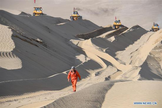 Worker Li Mingyou walks on a dune at the construction site of a road connecting Yuli and Qiemo counties, northwest China's Xinjiang Uygur Autonomous Region, May 16, 2020. It is the third road crossing the Taklimakan Desert, the world's second-largest shifting desert. Xinjiang has invested 397.3 billion yuan (around 58.3 billion U.S. dollars) between 2014 and 2019 in road construction, local authorities said. This was 1.53 times the total investment in road construction in Xinjiang between 1949 and 2013, said the regional transport department. (Xinhua/Song Yanhua)