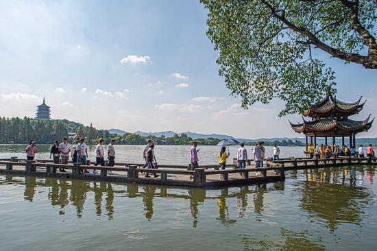 Tourists visit the West Lake scenic area in Hangzhou, east China's Zhejiang Province, Oct. 1, 2020. (Photo by Jiang Han/Xinhua)