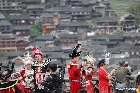 Tourists wearing costumes pose for photos beside a village of Miao ethnic group in Qiandongnan Miao and Dong Autonomous Prefecture of southwest China's Guizhou Province, Oct. 7, 2020. (Photo by Lin Shikang/Xinhua)