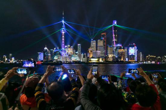 People enjoy a light show at the Bund in east China's Shanghai, Oct. 5, 2020. (Xinhua/Wang Xiang)