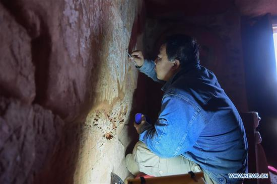 A staff worker restores fresco in Arjai Grottoes in Otog Banner of Ordos, north China's Inner Mongolia Autonomous Region, Oct. 8, 2020. Cultural heritage workers started restoring the frescoes in the 1,600-year-old Arjai Grottoes in 2018. The site has 65 grottoes. Of the 41 grottoes that have remained intact, 14 feature frescoes. Ten grottoes featuring frescoes have been restored. (Xinhua/Li Zhipeng)