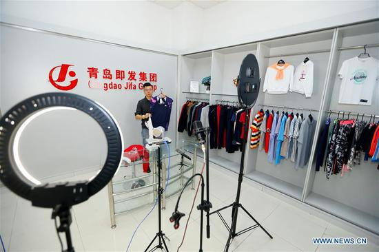 A staff member of Qingdao Jifa Group presents apparel products via the livestreaming platform of online Canton Fair in Qingdao, east China's Shandong Province, Oct. 15, 2020. The 128th edition of the China Import and Export Fair, popularly known as Canton Fair, kicked off online in south China's Guangdong Province on Thursday. It is the second time that the fair has moved online this year due to the COVID-19 outbreak. The previous online session was held in June. The 10-day event has attracted around 26,000 domestic and overseas enterprises, with more than 2.35 million products spanning 50 exhibition areas in 16 categories. (Photo by Liang Xiaopeng/Xinhua)