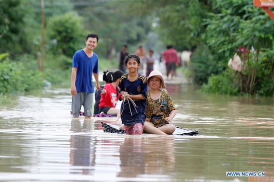 People walk through a flooded street in Dangkor district in the Southwestern suburb of Phnom Penh, Cambodia on Oct. 15, 2020. Thirteen people have been killed and 12,376 others evacuated in Cambodia after a tropical storm-triggered rains caused flash floods in 19 of the kingdom's 25 cities and provinces, a spokesman said on Thursday. (Photo by Phearum/Xinhua)