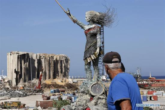 A man passes by a statue of a lady near the Beirut port in Lebanon, Oct. 20, 2020. Lebanese artists create a statue of a lady by using the rubbles of the Beirut port explosion, with a clock stopping at the moment of the explosion at about 6:08 p.m. on Aug. 4, 2020. (Xinhua/Bilal Jawich)