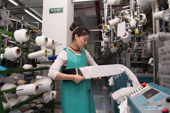A worker checks on fabric quality at a sock company in Datang community of Zhuji, east China's Zhejiang Province, Oct. 27, 2020. Sock companies in Datang, a major sock manufacturing base, began to see a rebound in business in the second half of the year. (Xinhua/Sadat)
