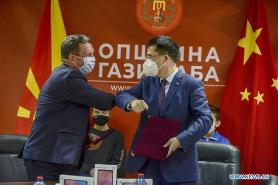 Chinese Ambassador to North Macedonia Zhang Zuo (R) touches elbow with mayor of Municipality Gazi Baba Borce Georgievski (L) during a signing ceremony of an agreement in Skopje, North Macedonia, Oct. 29, 2020. Chinese embassy in North Macedonia donates 310 tablets to school kids to help them have on-line classes. (Photo by Tomislav Georgiev/Xinhua)