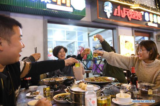 Tourists enjoy dinner at a night market in Shouchang Township of Jiande City, east China's Zhejiang Province, Nov. 10, 2020. Shouchang, a small town in mountainous area of Zhejiang, has set up a special night market bringing together night-time booths and more than 30 restaurants, in an effort to enrich people's leisure time and boost local economy. The night market has received over 720,000 tourist trips and raked in 76.33 million yuan (about 11.57 million U.S. dollars) since it opened during the Labor Day holiday. (Xinhua/Weng Xinyang)