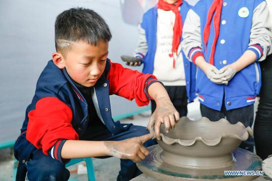Primary school students try porcelain making at a workshop of Ru porcelain in Baofeng County, central China's Henan Province, Nov. 15, 2020. Baofeng County is famous for producing Ru porcelain, one of the five famous porcelains during the Song Dynasty (960-1279) in ancient China. More than 90 students of Xichengmen Primary School in Baofeng County took part in a practical activity here on Sunday to learn about Ru porcelain. (Photo by He Wuchang/Xinhua)