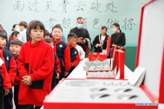 Primary school students view porcelain works at a workshop of Ru porcelain in Baofeng County, central China's Henan Province, on Nov. 15, 2020. Baofeng County is famous for producing Ru porcelain, one of the five famous porcelains during the Song Dynasty (960-1279) in ancient China. More than 90 students of Xichengmen Primary School in Baofeng County took part in a practical activity here on Sunday to learn about Ru porcelain. (Photo by He Wuchang/Xinhua)