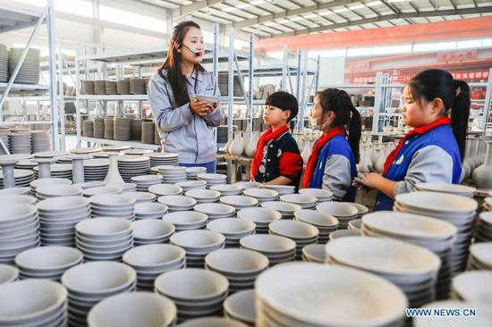 Primary school students learn about porcelain works at a workshop of Ru porcelain in Baofeng County, central China's Henan Province, on Nov. 15, 2020. Baofeng County is famous for producing Ru porcelain, one of the five famous porcelains during the Song Dynasty (960-1279) in ancient China. More than 90 students of Xichengmen Primary School in Baofeng County took part in a practical activity here on Sunday to learn about Ru porcelain. (Photo by He Wuchang/Xinhua)