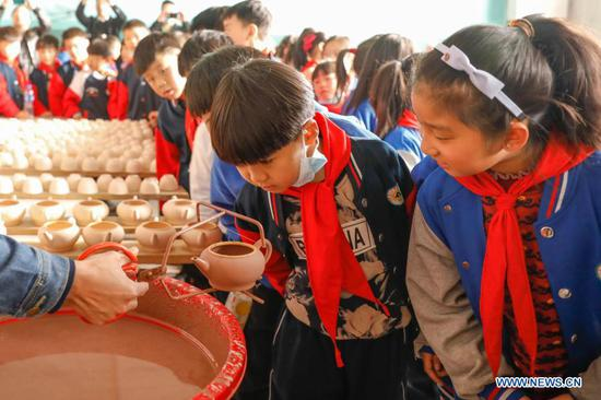 Primary school students view the production process of porcelain works at a workshop of Ru porcelain in Baofeng County, central China's Henan Province, on Nov. 15, 2020. Baofeng County is famous for producing Ru porcelain, one of the five famous porcelains during the Song Dynasty (960-1279) in ancient China. More than 90 students of Xichengmen Primary School in Baofeng County took part in a practical activity here on Sunday to learn about Ru porcelain. (Photo by He Wuchang/Xinhua)