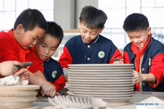 Primary school students try porcelain making at a workshop of Ru porcelain in Baofeng County, central China's Henan Province, on Nov. 15, 2020. Baofeng County is famous for producing Ru porcelain, one of the five famous porcelains during the Song Dynasty (960-1279) in ancient China. More than 90 students of Xichengmen Primary School in Baofeng County took part in a practical activity here on Sunday to learn about Ru porcelain. (Photo by He Wuchang/Xinhua)
