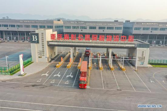 Aerial photo taken on Nov. 17, 2020 shows a cross-border highway regular lorry for Kazakhstan leaving the Nanpeng Highway Bonded Logistics Center in southwest China's Chongqing Municipality. The logistics center sent its first cross-border highway regular lorry for Kazakhstan on Tuesday. To date, several road freight transportation routes, including Chongqing-Singapore, Chongqing-Myanmar, and Chongqing-Vietnam services, have been made available. Cargos with a total worth of 1.158 billion yuan (about 176 million U.S. dollars) have been delivered through these highway lorries so far this year. (Xinhua/Huang Wei)