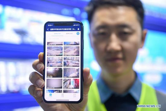 An engineer for the First Company of the China Construction Third Engineering Bureau displays the mobile interface of a smart monitoring system in Nanjing, east China's Jiangsu Province, Nov. 17, 2020. Constructors of the Jinling Zhonghuan construction project have recently adopted a
